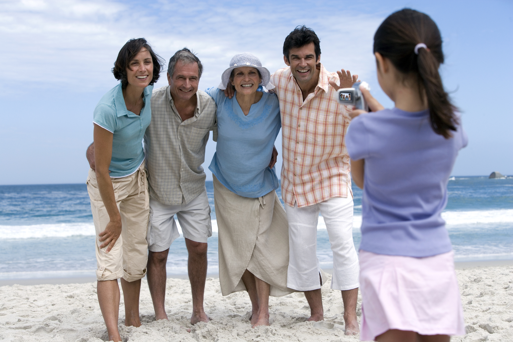 Multigenerational family taking a video on the beach